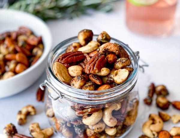 A jar and white bowl with Sweet and Spicy Nuts with nuts also on the white marble benchtop. Sprigs of rosemary and a glass of gin with a slice of lime are in the background.