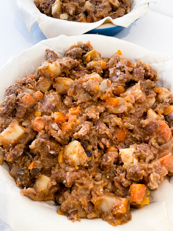 A pastry lined round pie dish filled with Beef and Vegetable filling.
