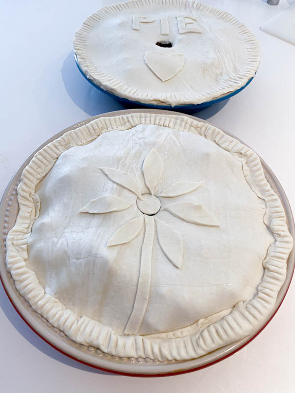 2 round pie dishes that are both uncooked and ready to go into the oven. One is decorated with a flower made of pastry and the other has the word 'pie' and a heart on it.