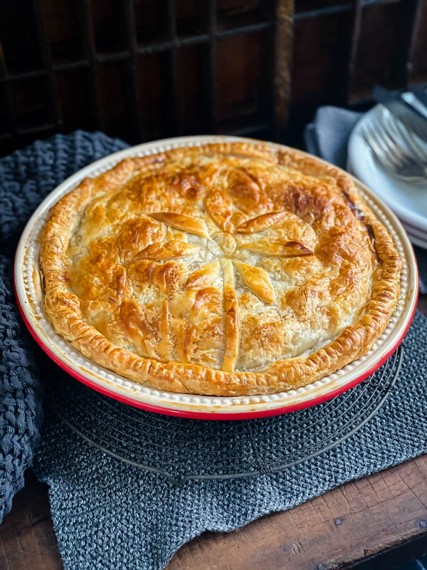 A cooked Beef and Vegetable family sized pie in a red ceramic pie dish, sitting on a wooden table on top of a wire resting rack.