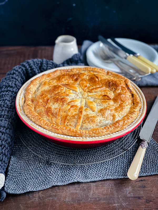 A family sized Beef and Vegetable Pie sitting on top of a resting rack on a dark wooden table with plates, cutlery and napkins in the photo.