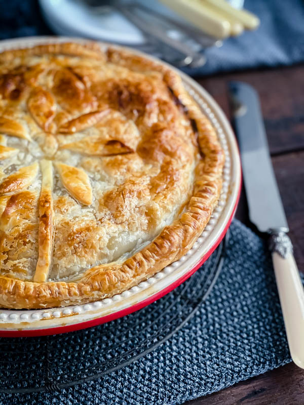 Close up of a Beef and Vegetable Pie which is only half in the photo with a knife next to it.