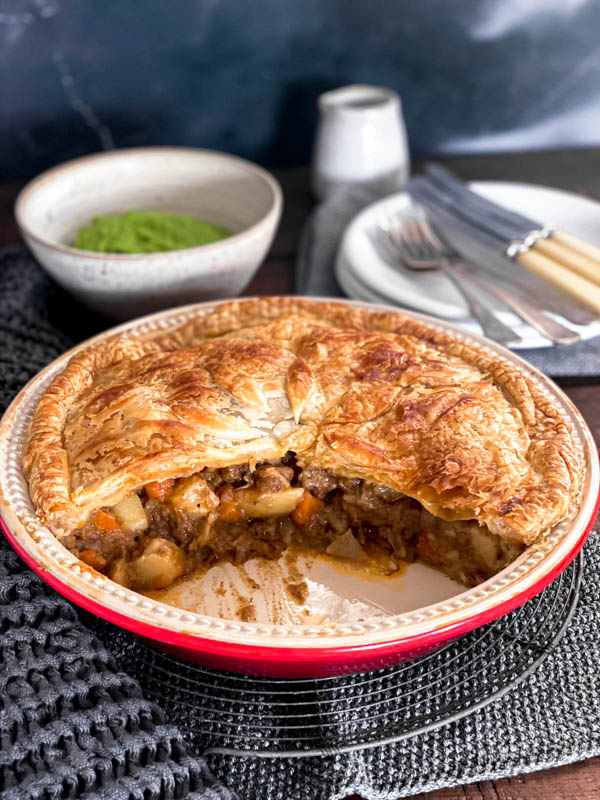 A family size Beef and Vegetable Pie that has had a wedge of pie removed so you can see the filling inside. Behind the pie are white plates, cutlery and a bowl of pea puree.