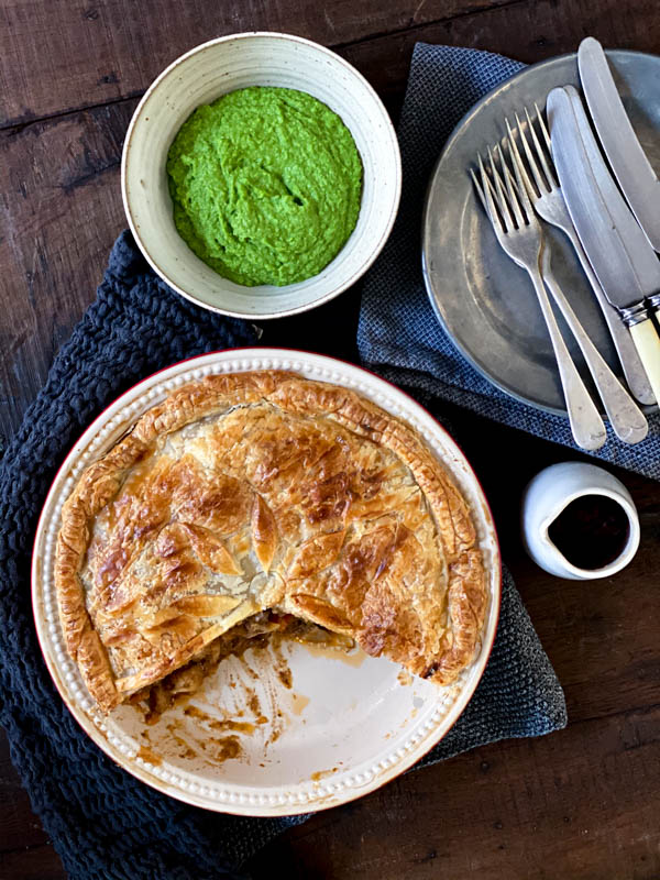 Looking down onto the Beef and Vegetable pie that has had a wedge taken from it, with a bowl of pea puree in the background. There is also a pewter plate with cutlery on top of it and a small jug of tomato sauce.