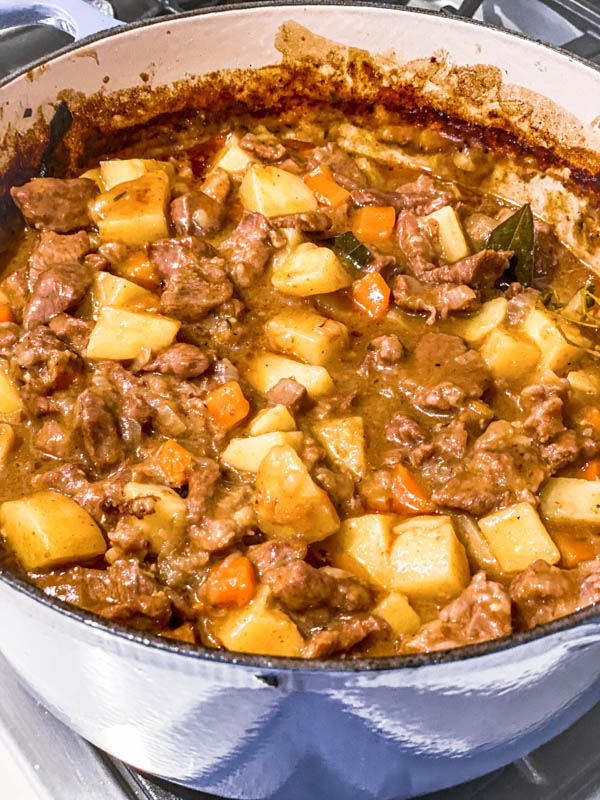 A blue Le Creuset Dutch oven filled with Beef and Vegetable filling, cooked and ready to be chilled.