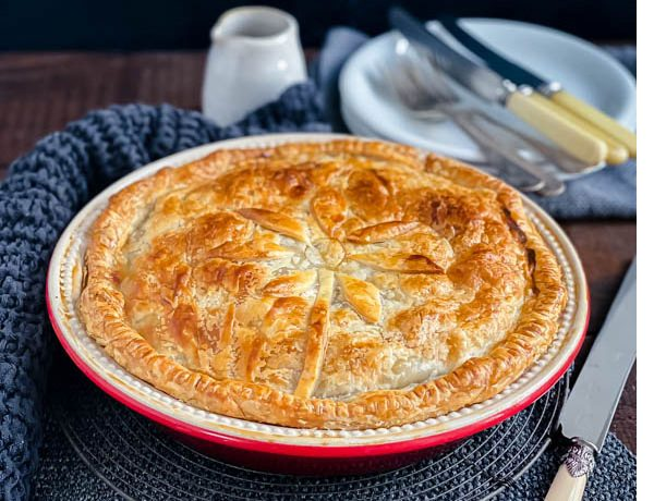 The family sized round Beef and Vegetable Pie on a dark wood table with white plates and cutlery in the background and a knife beside it.