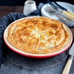 A round family sized Beef and Vegetable Pie on a round resting rack on top of a dark wood table with plates and cutlery in the background.
