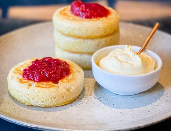 A grey ceramic plate with 3 stacked sourdough crumpets on it. In the front of them and still on the plate is another crumpet with a small bowl of creme fraiche. On top of the stack and on the single crumpet are dollops of rhubarb compote.