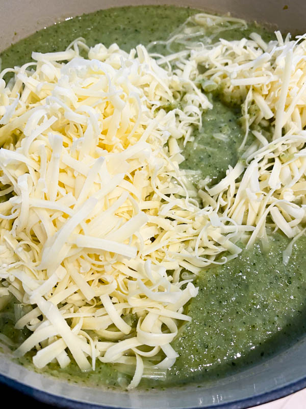This shows the blended soup back in the cleaned pot with grated cheese on top, ready to be stirred through .