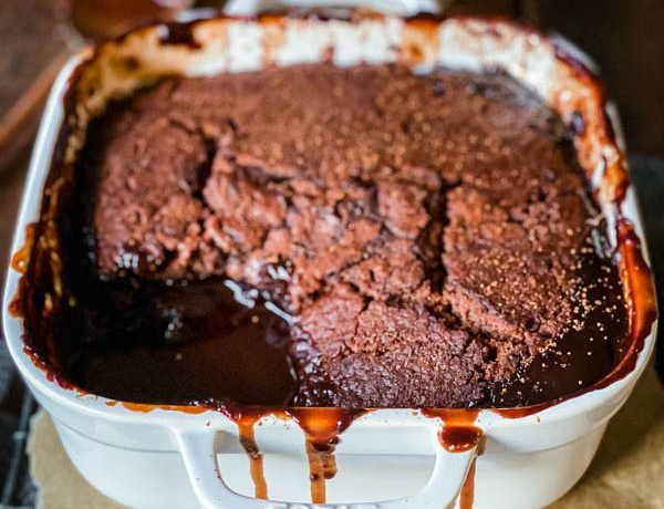 Close up of the Chocolate Self Saucing Pudding in a square, white ovenproof dish with gooey chocolate sauce visible in the bottom of the dish.