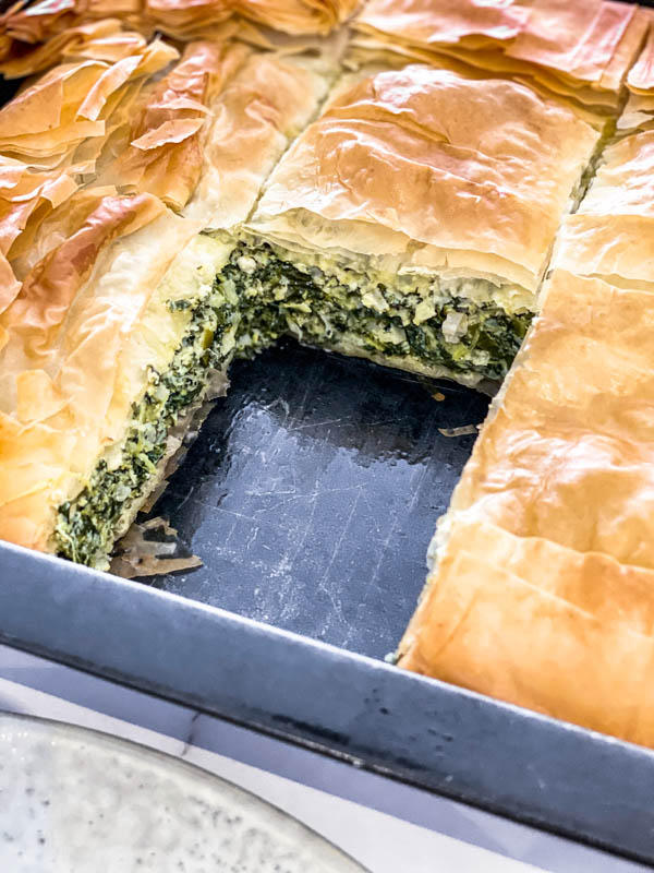 One serve of Spanakopita Pie is removed to show the inside of the pie.