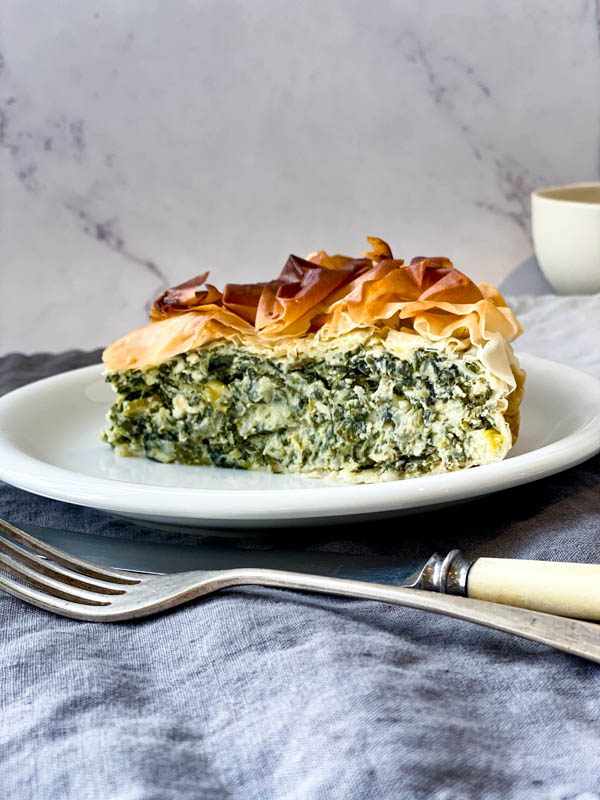 A slice of Spanakopita Pie on a white plate with a knife and fork in front of the plate. The plate is on a grey blue linen tablecloth.