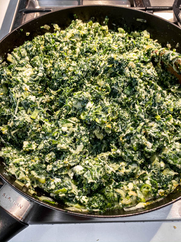 The Spanakopita Pie filling of spinach, cheeses, onions, leeks and herbs are all mixed together in a frying pan ready for filling the pie.