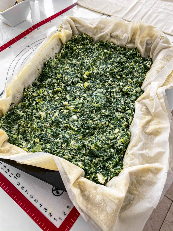 The filo pastry sheets are buttered and laid out in a rectangle baking dish with the Spanakopita Pie filling inside, ready for the top layers of filo to be added.
