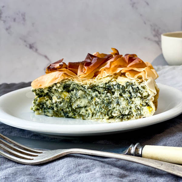 A slice of Spanakopita Pie sitting on a white small plate with a knife and fork in the foreground and draped linen napkins in the background.