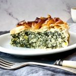 A wedge of Spanakopita Pie served on a white plate with knife and fork in front.