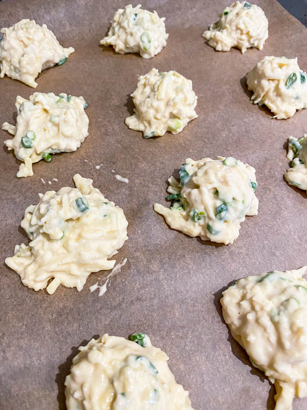 Dollops of Cheese Puff batter are on a baking paper-lined baking tray ready to be baked in the oven.