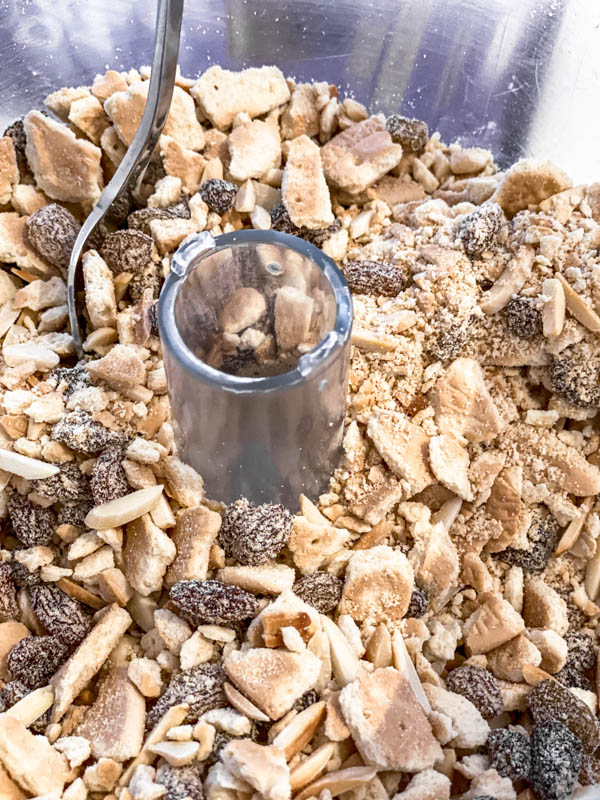 The crushed biscuits, sultanas, nuts and coconut are in the bowl of a food processor.