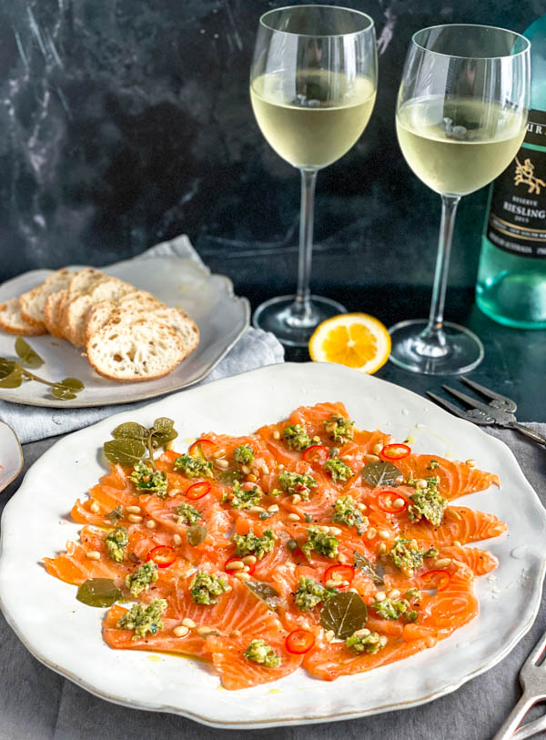 A close up of the platter of thinly sliced sashimi salmon topped with dollops of the chunky tartare mix. In the background are 2 glasses of wine, baguette slices and a lemon half, all on a black marble bench.