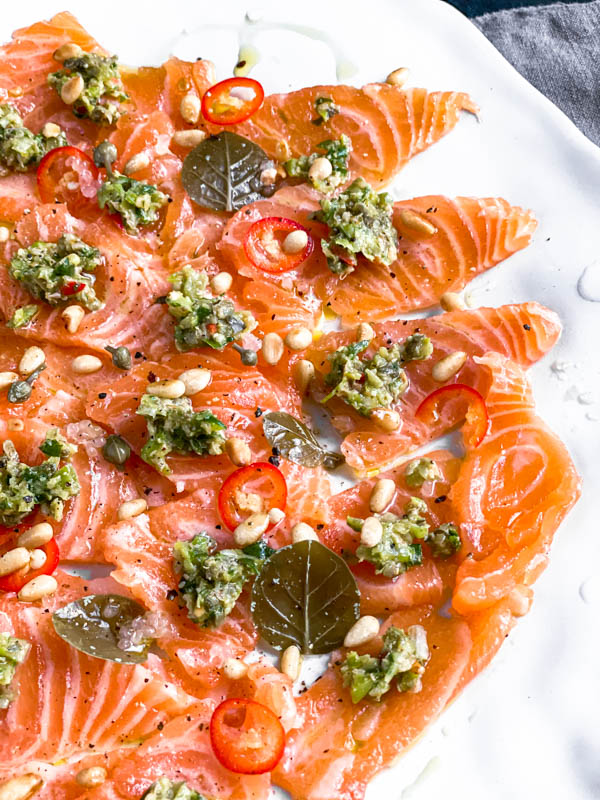 A close up of the thinly sliced salmon sashimi with dollops of tartare on top of the salmon pieces, along with slices of red chilli, pinenuts and caper berries and leaves.