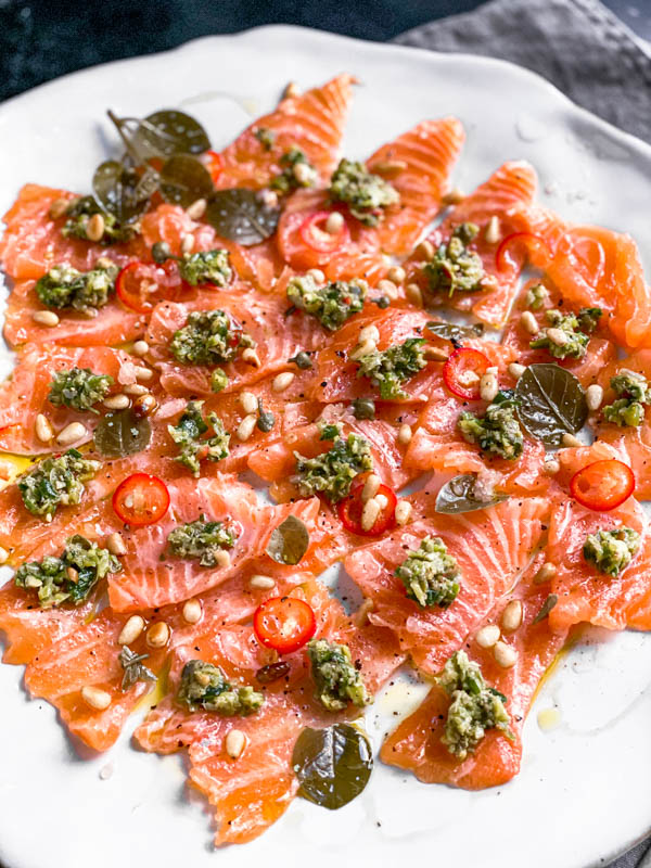 The platter of thinly sliced salmon sashimi pieces with the dollops of tartare on top. It also has sliced red chillies, pinenuts, capers and caper leaves scattered over the salmon. The whole plate is drizzled with olive oil.