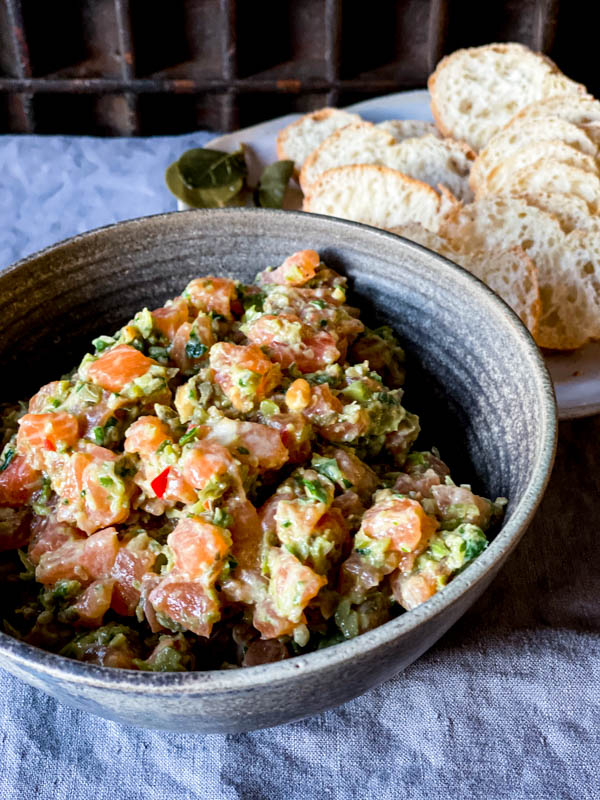 A ceramic bowl of Salmon Tartare with some thinly sliced baguette rounds behind it on a plate.
