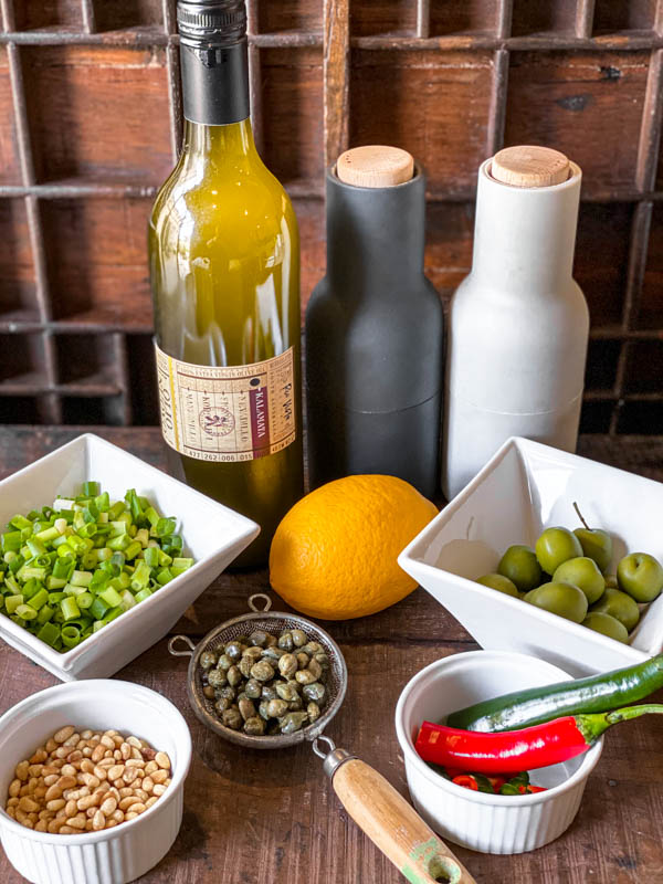 A photo showing all the ingredients required to make the Salmon Tartare dressing: a bottle of olive oil, salt and pepper shakers, sicilian olives, chillies, a lemon, a small strainer with salted capers, toasted pinenuts, chopped spring onions.
