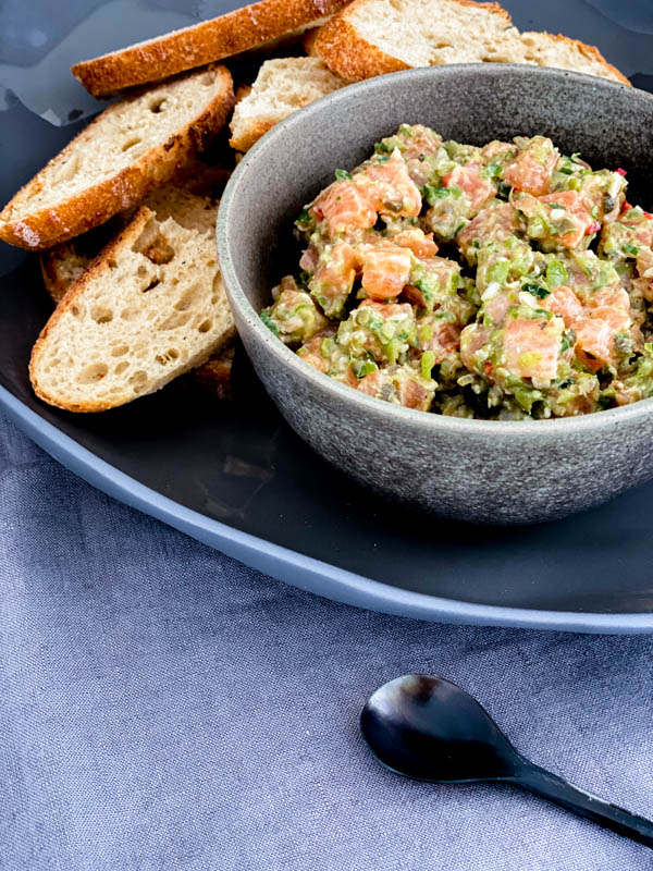 A bowl of Salmon Tartare on a platter with thinly sliced sourdough bread beside it.