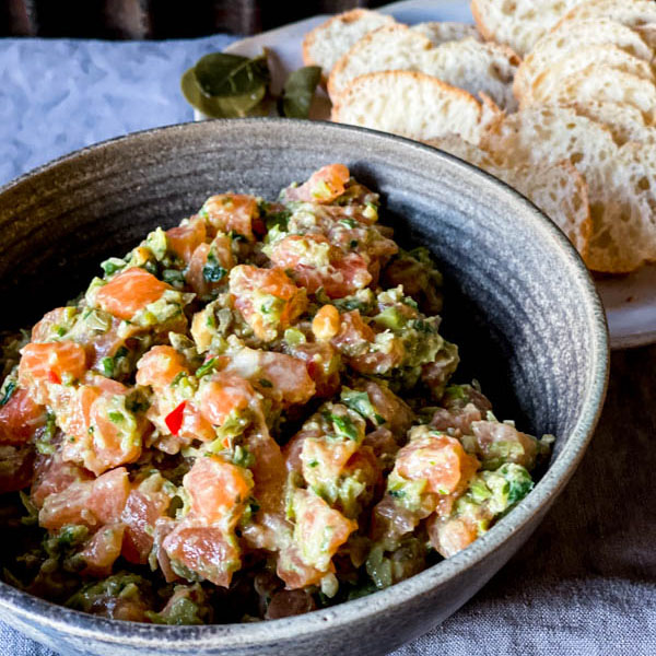A bowl of Salmon Tartare on a grey tablecloth with thinly sliced bread rounds behind it on a plate.