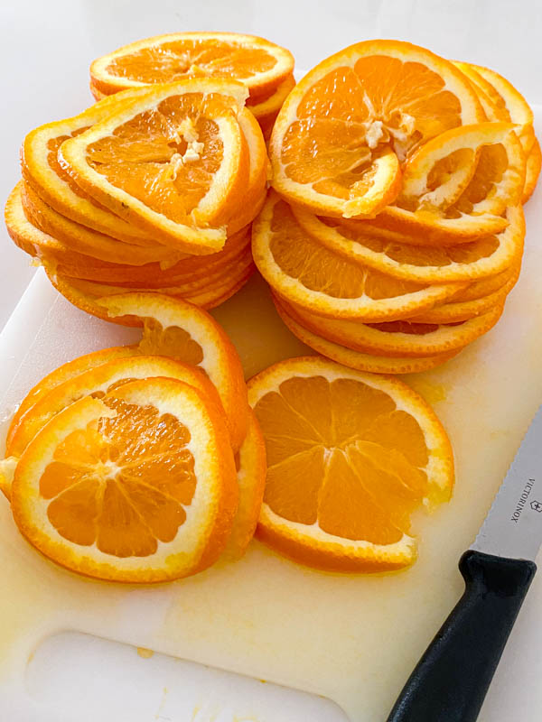 A pile of thin orange slices from 4 oranges sitting on a chopping board.