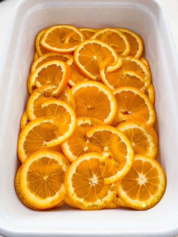 The orange slices are placed in layers in a large rectangle baking dish.