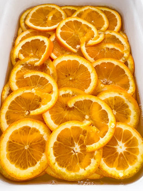 The reduced sugar syrup has now been poured over the orange slices in the large baking dish so they are all covered.