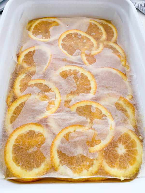 A piece of baking paper large enough to fit into the rectangle baking dish, is placed over the orange slices and syrup and pressed down lightly.
