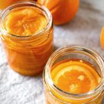 Two jars of confit orange slices in syrup with whole oranges in the background.