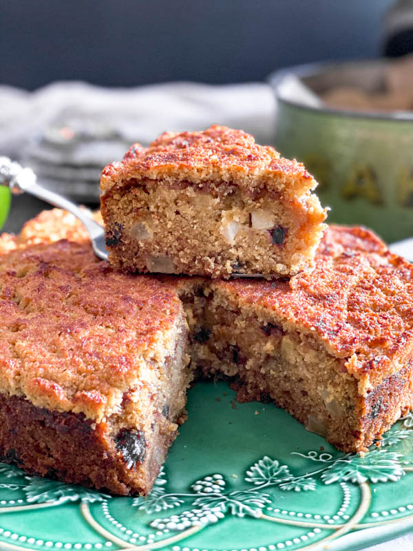 The cake has a slice removed from it so you can see the inside of the cake, showing bits of apple and dates and a very moist, dense crumb.