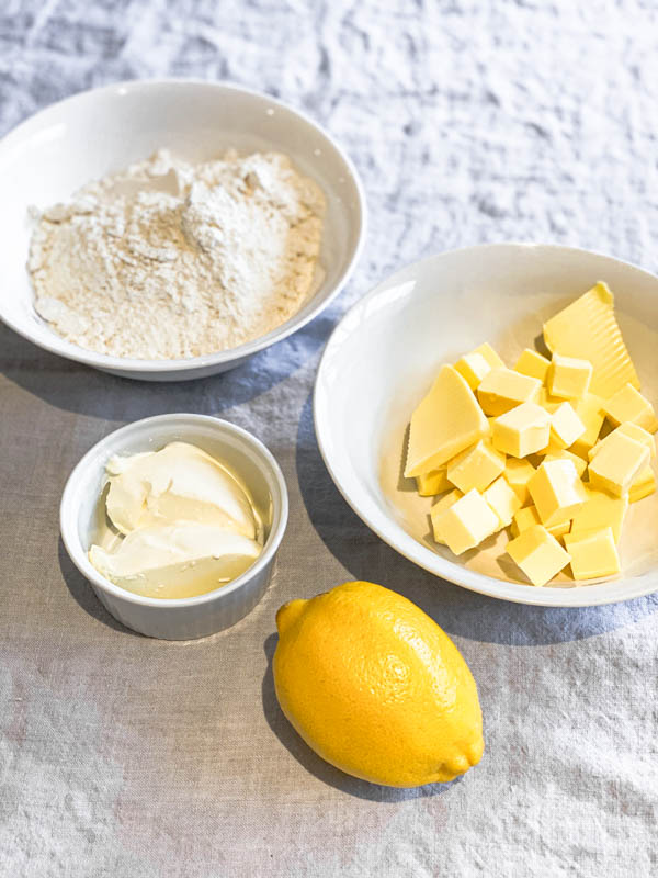Bowls of ingredients (butter, flour, sour cream) and a lemon to make the Sour Cream Pastry for the galette.