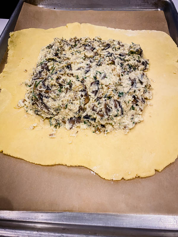 The pastry is rolled out to a 30cm rough circle, with the cheese filling spread out in the middle leaving a 3-4cm border around the outside. The cheese mixture has had 1/2 of the mushrooms mixed into it.