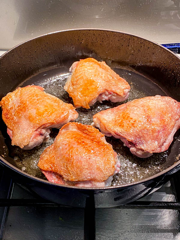 The chicken thighs have been browned on the skin-side and are now turned over to seal the underside.