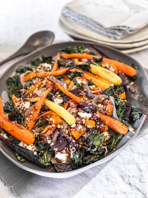 A platter of Roasted Vegetable Salad with Quinoa and Feta, on a table with a serving spoon to the side and plates and napkins in the background.