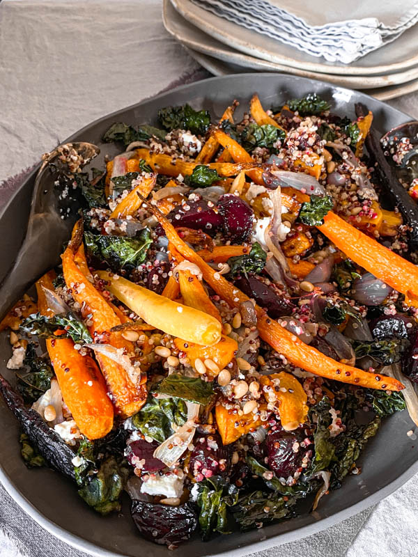 A close up of the Roasted Vegetable, Quinoa and Feta Salad with plates and napkins behind it.