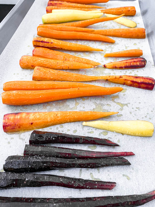 Baby heirloom carrots that have been oiled and salted are spread out on an oven tray.