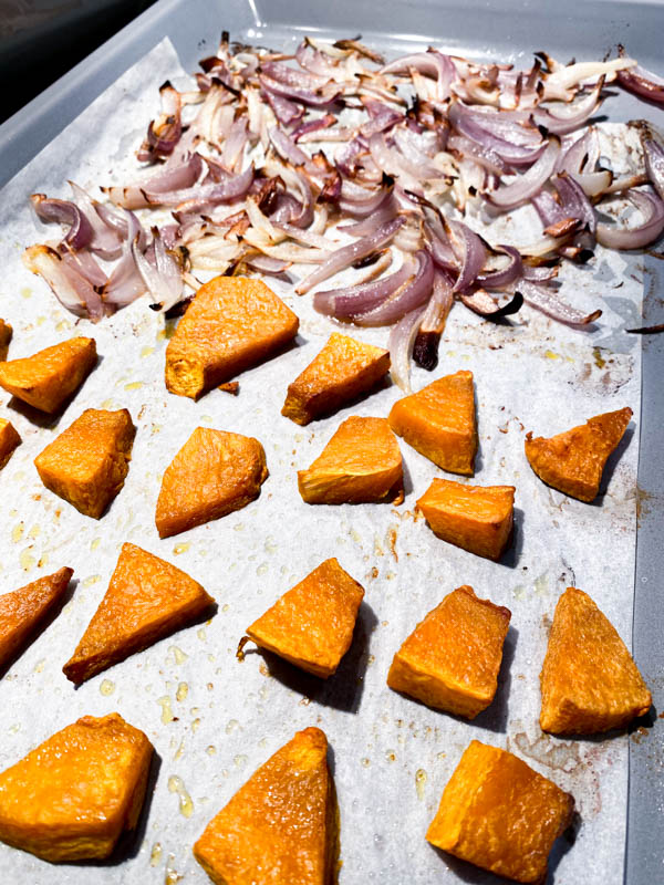 Pumpkin pieces and onion wedges that have been roasted are on an oven tray.
