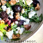 The Roast Beetroot, Goats Cheese and Walnut Salad is dressed and on a white platter with rocket (arugula) leaves.