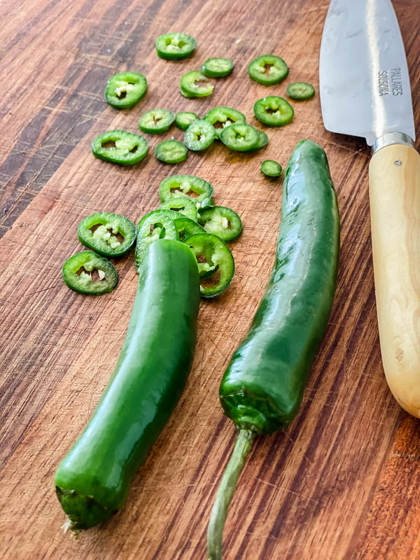 Green Chillies are being sliced on a wooden chopping board.