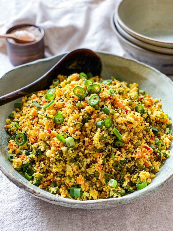 The Cauliflower Fried Rice with Turmeric is in a green ceramic bowl on a table with a serving spoon. In the background are 3 stacked bowls and a pinch bowl of salt.