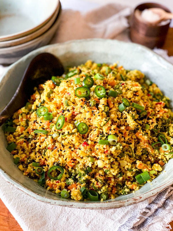 The Cauliflower Fried Rice with Turmeric is in a serving bowl on a folded napkin with bowls and salt in the background.