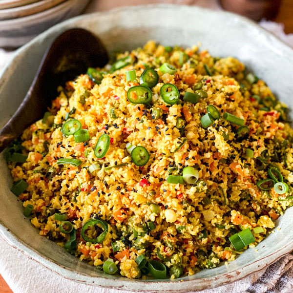 The prepared Cauliflower Fried Rice with Turmeric is in a salad bowl with a serving spoon.