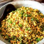 The Cauliflower Fried Rice with Turmeric is in a Salad bowl on a table with bowls in the background and a pinch bowl of sea salt.