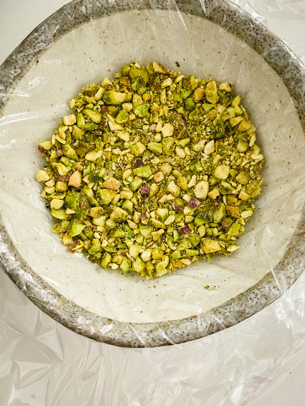 The chopped pistachio nuts are in a small bowl that has been lined with cling wrap.