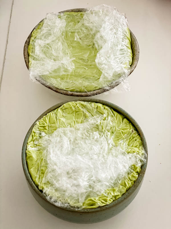 This shows both small bowls now filled with the avocado pate and covered in cling wrap. The bowls are now ready to be placed in the fridge.